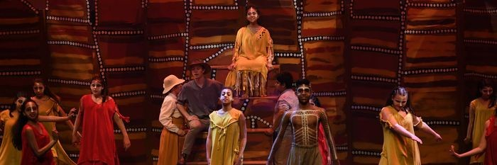 Students in costume performing on stage with an aboriginal themed backdrop showing earthy colours.