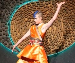 Student in bright orange costume performing  a dance.