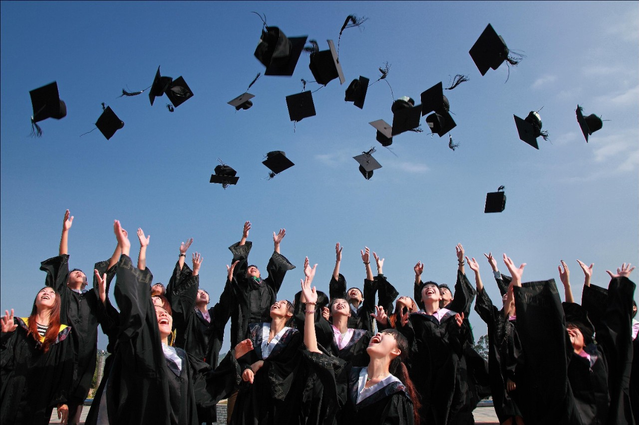 Graduates throwing their hats into the air in celebration