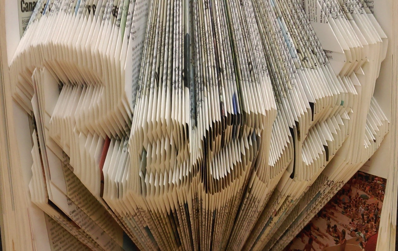 A book whose pages have been folded into the word 'read'.